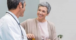 Older woman smiling at male doctor wearing white coat and stethoscope around neck