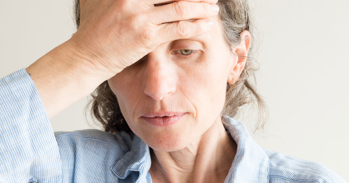 Older woman looking tired with hand on forehead