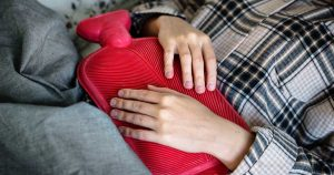 Woman laying in bed with hot water bottle