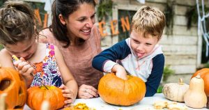 Mom sitting with her children carving pumpkins