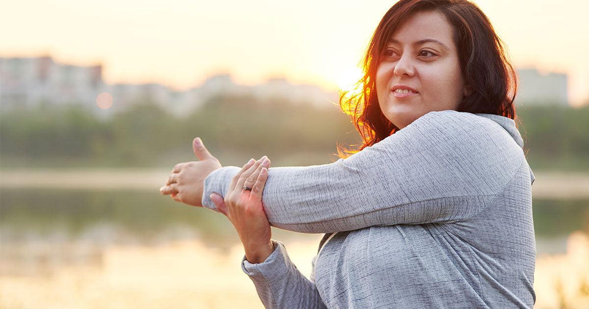 Woman crossing one arm over body in a stretch while outside