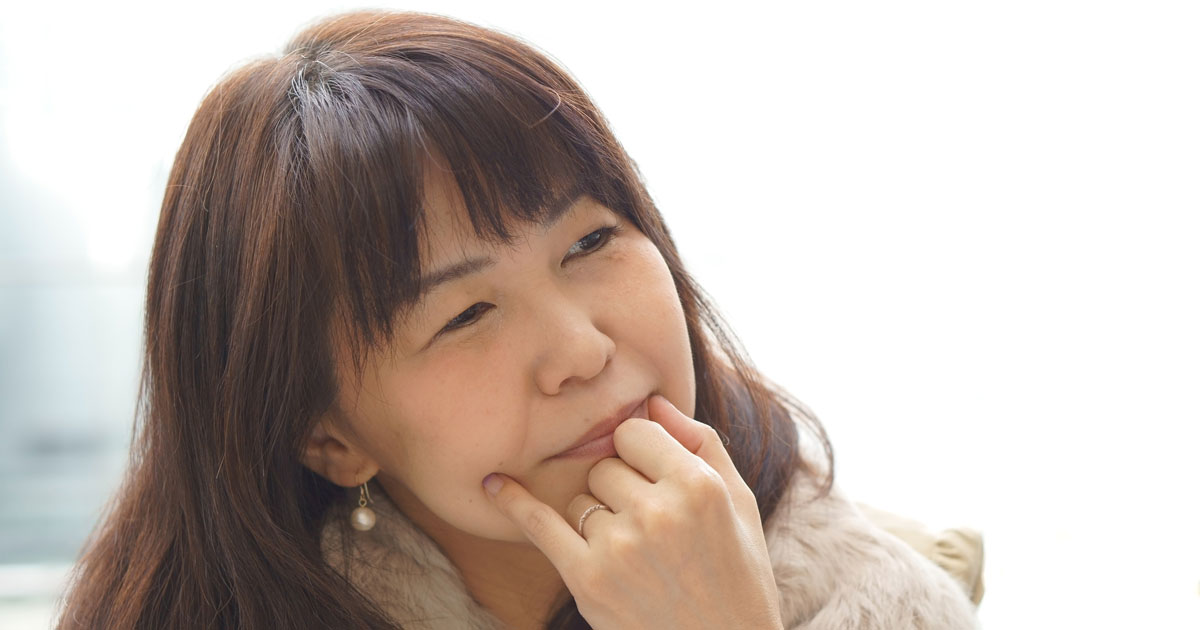 Woman looking thoughtful with hand on chin