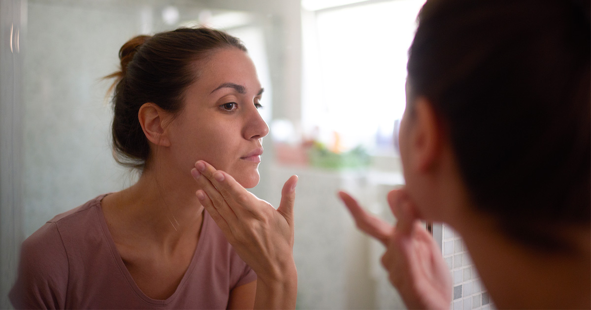 Woman touching her cheek while looking in the mirror