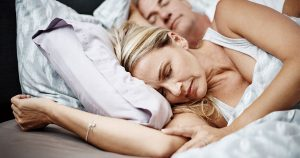 Woman sleeping with husband sleeping in background