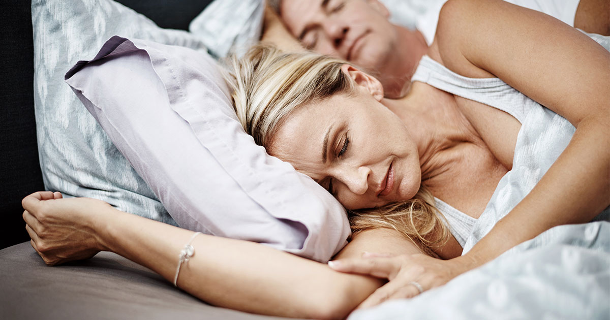 Woman sleeping with husband sleeping in background