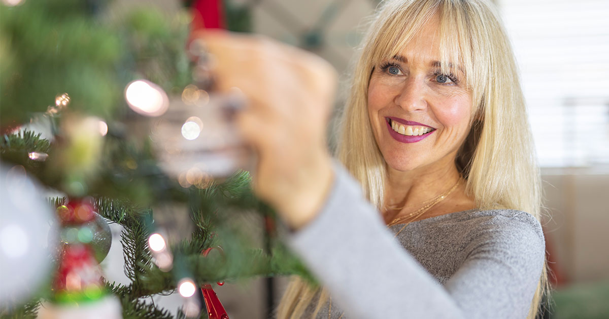 Woman hanging ornament on Christmas tree