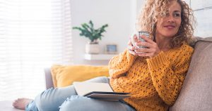 Woman sitting on couch drinking out of a mug with notebook in her lap
