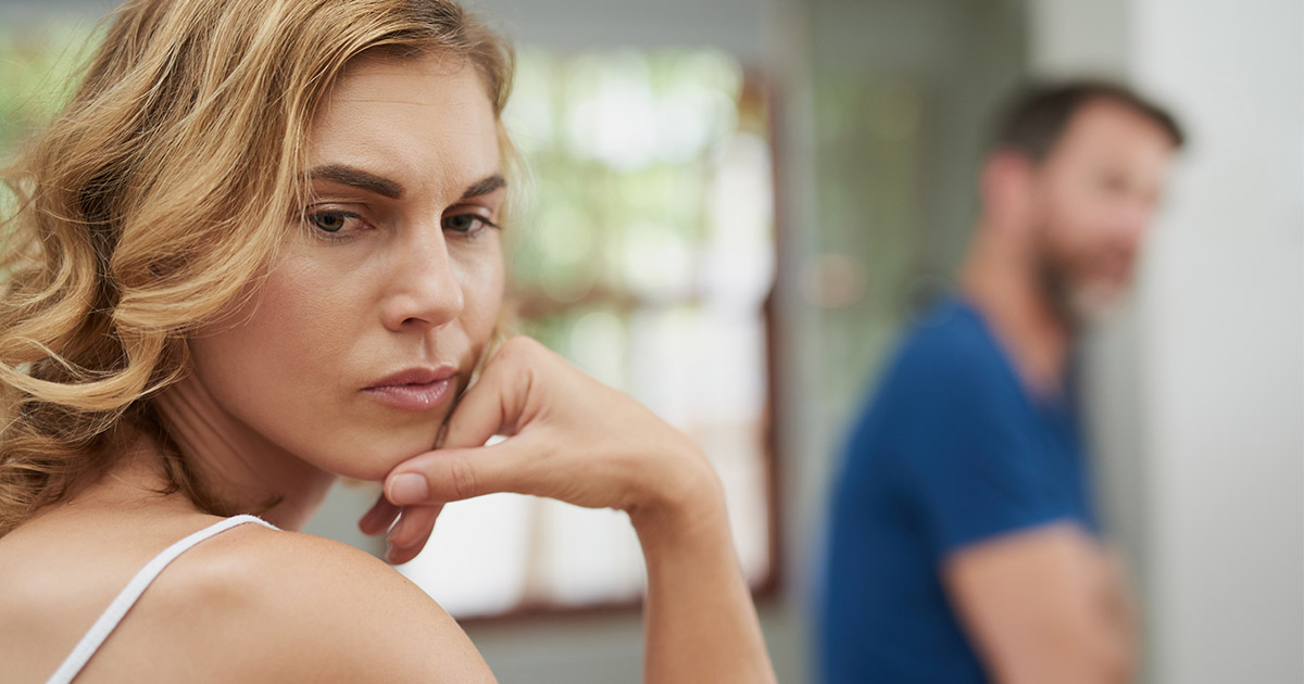Woman looking angry with man in background