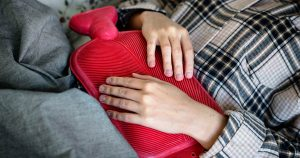 Woman lying with a hot water bottle on her stomach