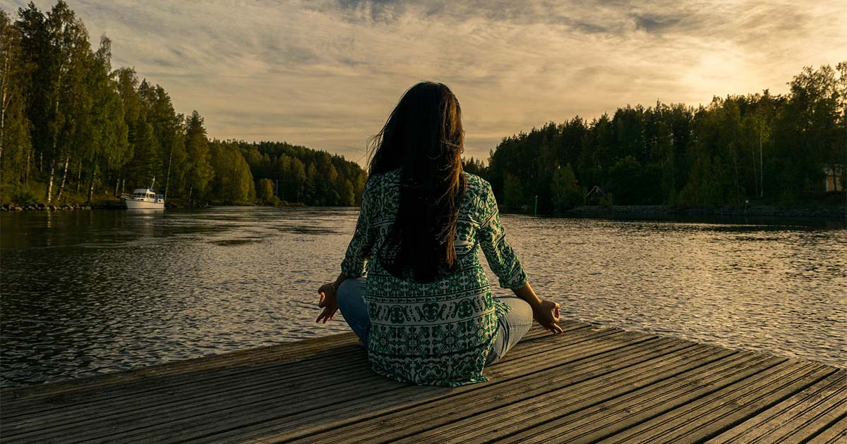 Woman sitting on a dock doing yoga