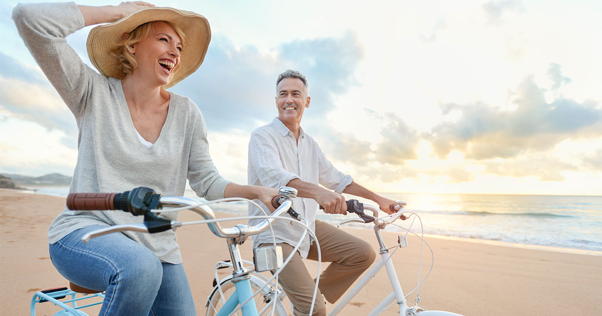 Woman and man riding bikes on the beach