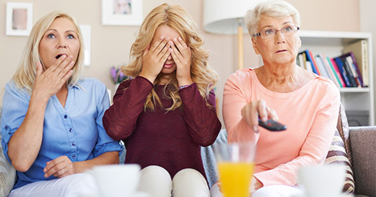 Two women staring in shock at TV with the third covering her eyes