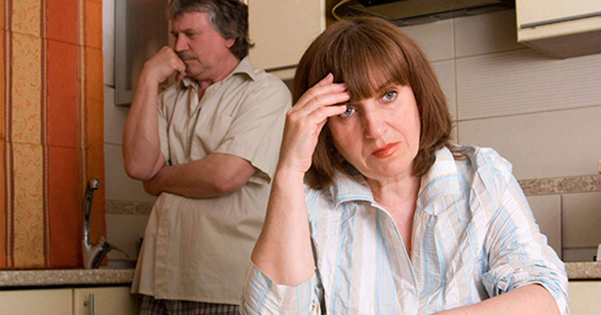 Woman sitting with her back to her husband, both looking frustrated