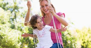 Mother pushing daughter on a swing