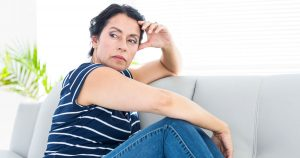Woman looking upset, sitting on couch