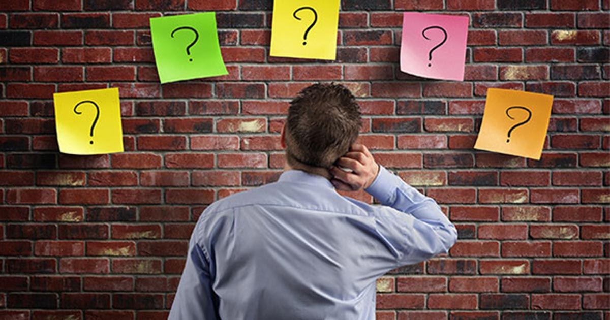Man standing at wall with question marks hanging on it