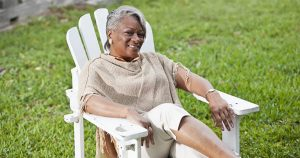 Older woman sitting in white lawn chair outside