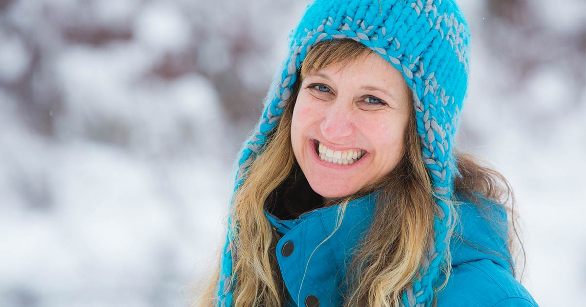Woman wearing hat in jacket smiling outside in the winter