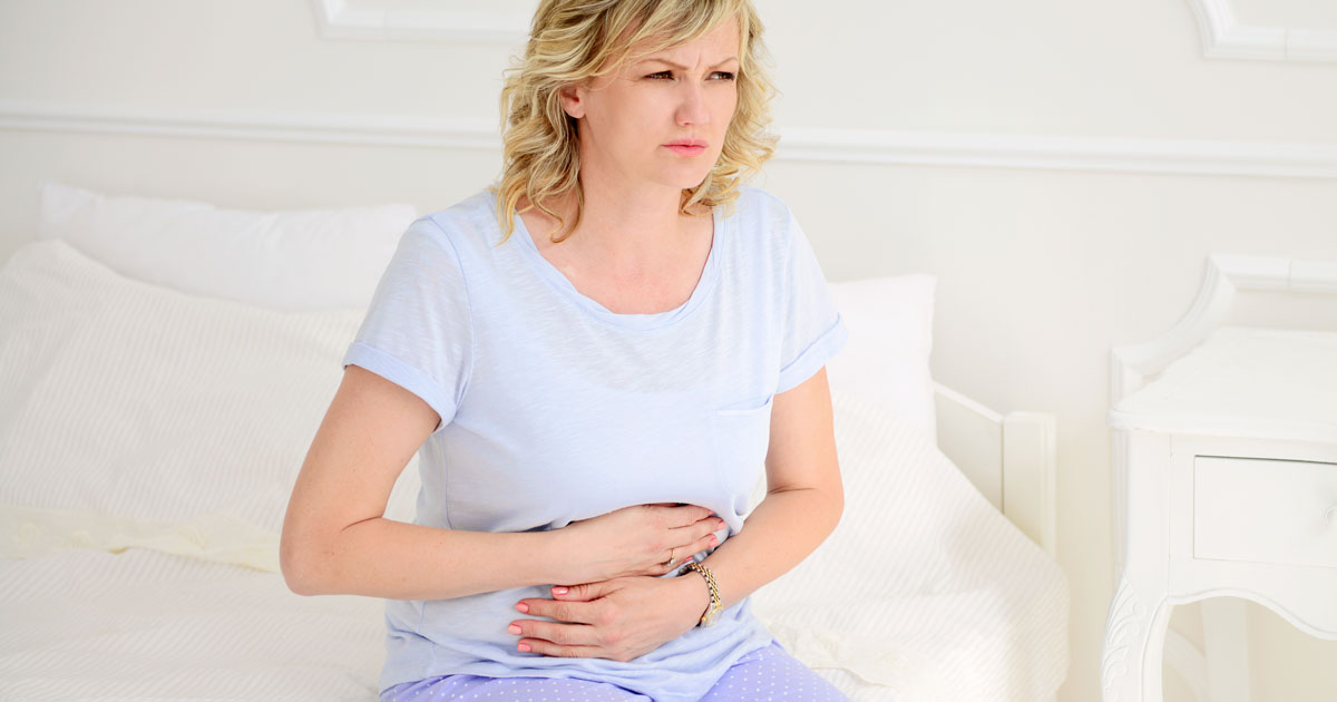 Woman looking like she is pain, holding her stomach