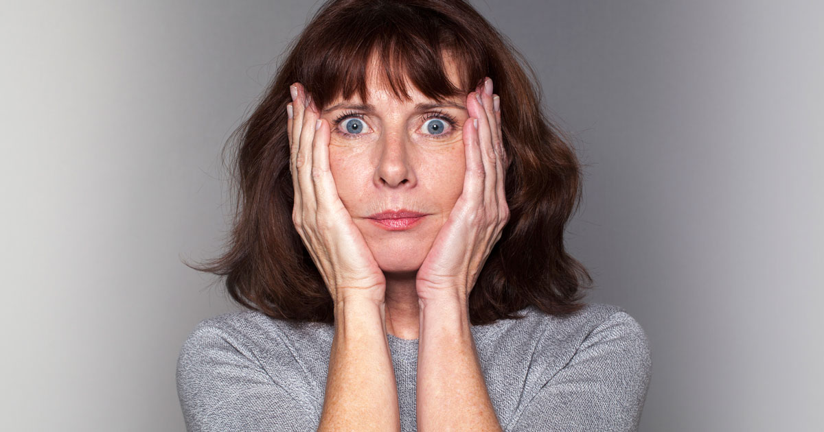Woman looks worried with hands pressed to either side of her face