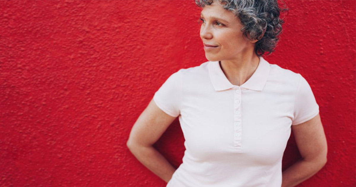 Older woman standing against red wall