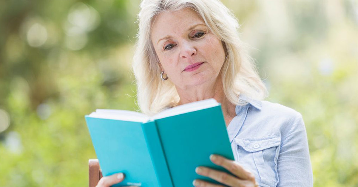 Older woman reading a book outside