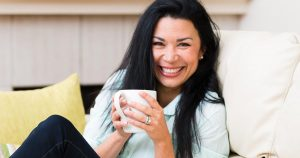 Woman sitting on couch, smiling and holding a white mug