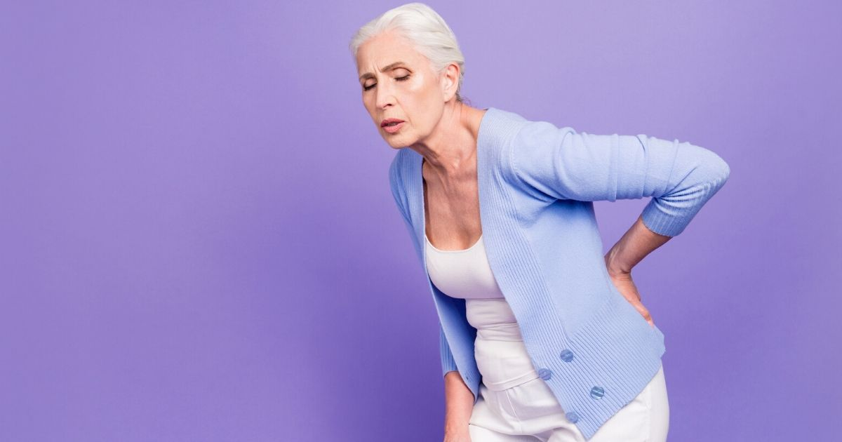 a woman experiencing back pain from post menopausal osteoporosis